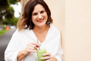 Photo of Vanessa Barrington, Founder of The Right Remark leaning against a cafe wall holding a green smoothie